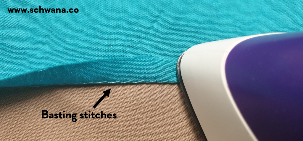 Folding and pressing the hem so that the basting stitch is not visible on the outside.
