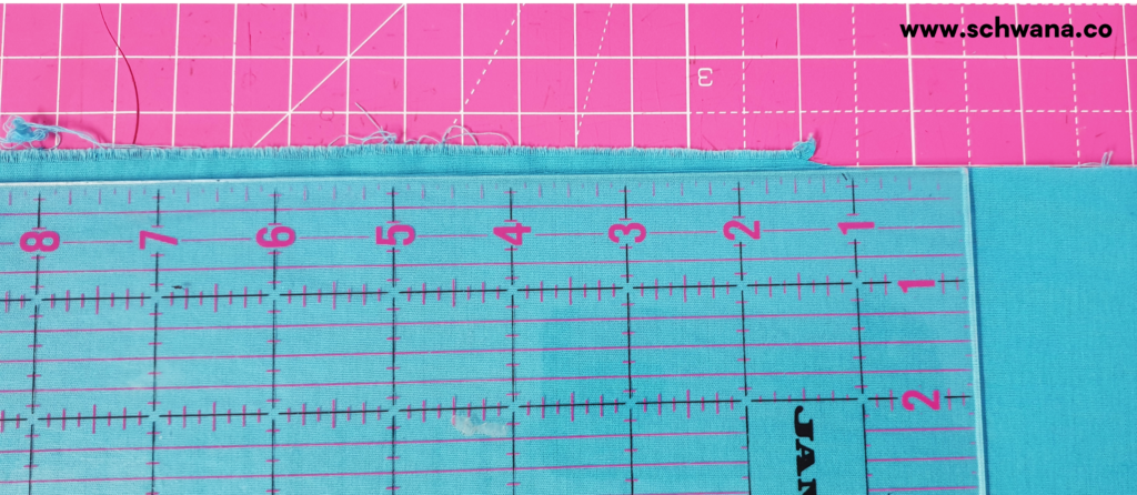 Placing the ruler on the folded fabric to help you cut a clean, straight line.