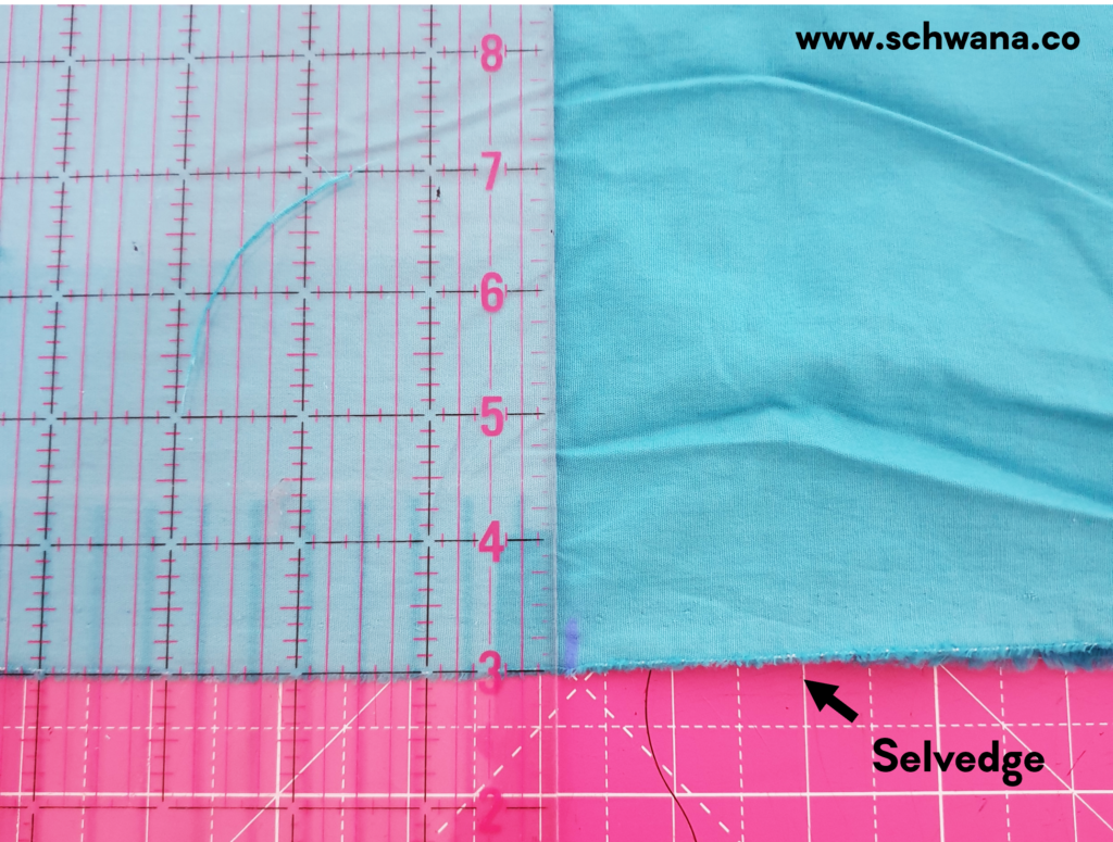 Showing how to cut perpendicular to the selvedge to create the first rectangle.