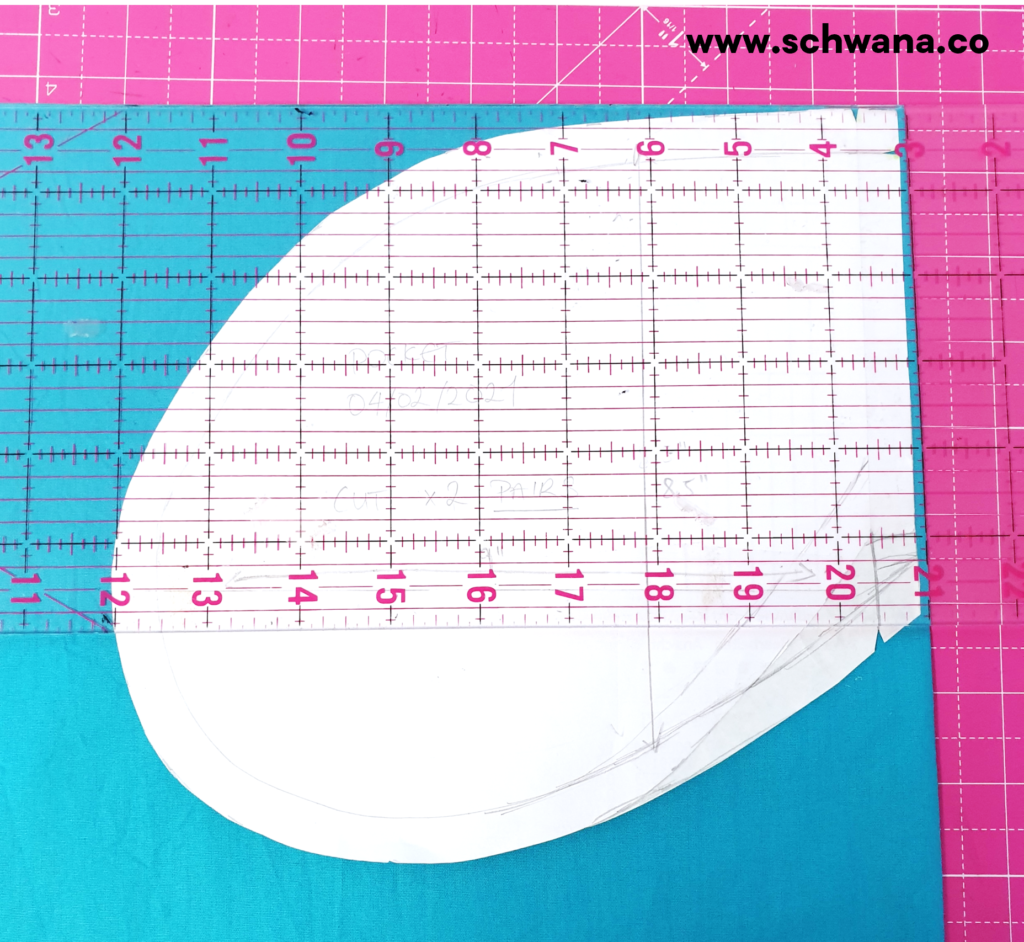 Placing the pocket pattern on the fabric and using the ruler to make sure the pocket is on grain.