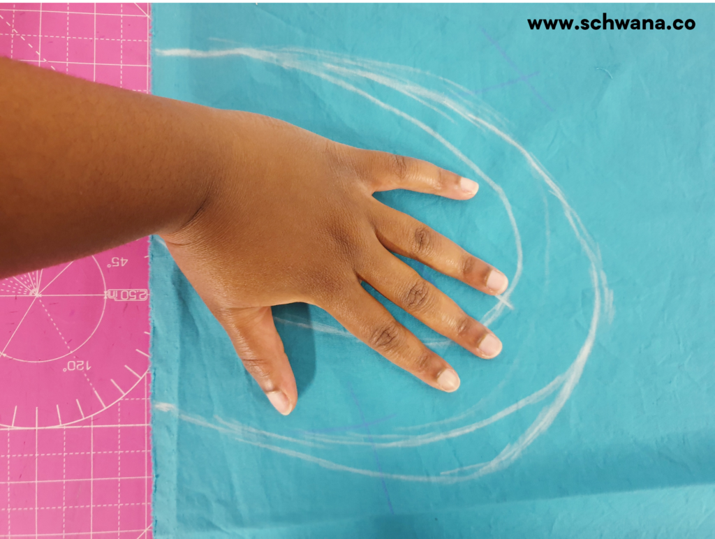 Placing my hand inside the drawn shape with my fingers stretched apart in order to make sure my hand will fit comfortably inside the pocket.
