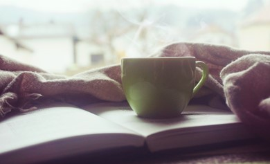Picture of a hot cup of tea or coffee on an open book. Relax and take breaks while sewing.